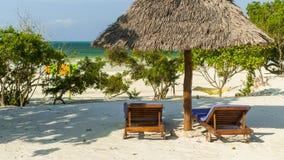 Två sunbeds och slags solskydd på den tropiska sandiga stranden. Semestra Arkivfoto