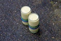 Två sunda drinkar, gula mangosmoothies på våt betong som reflekterar blå himmel Royaltyfri Bild