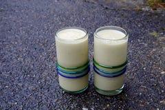 Två sunda drinkar, gula mangosmoothies på våt betong som reflekterar blå himmel Royaltyfri Fotografi