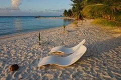 Två sunloungers på stranden på skymning franska Polynesien royaltyfri bild