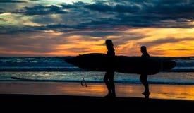 Två surfare på den Piha stranden i solnedgång arkivfoto