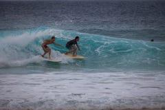 Två surfare på samma våg Arkivfoton