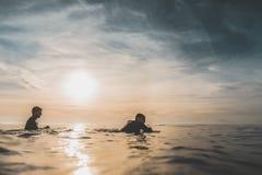 Två surfare som väntar på en våg på solnedgången arkivfoton