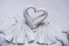 Två svanar som göras av handdukar som bildar blick som hjärta Shape på säng Arkivfoton