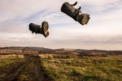 Två svarta kängor flyger över himlen i mitt av ett höstfält royaltyfri bild