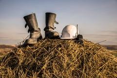 Två svarta kängor på en höstack på soliga kängor för en daytwosvart, en hjälm och en walkie-talkie på en höstack på en royaltyfri foto