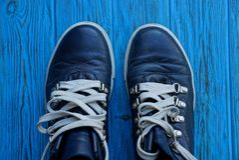 Två svarta skor med vit snör åt på ett blått bräde Fotografering för Bildbyråer