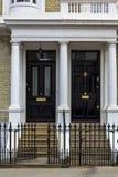 Två svarta trädörrar till bostads- byggnad i London Typisk d royaltyfri foto
