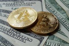 Två symboliska mynt av bitcoin på sedlar av hundra dollar Arkivfoton