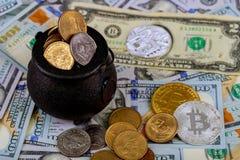 Två symboliska mynt av bitcoin på sedlar av hundra dollar kontant för en dollar Royaltyfri Foto