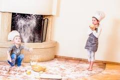 Två syskon - pojken och flickan - i hattar för kock` s nära spissammanträdet på kökgolvet som är nedsmutsat med mjöl som spelar m Arkivfoto