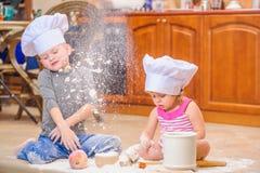 Två syskon - pojken och flickan - i hattar för kock` som s sitter på kökgolvet som är nedsmutsat med mjöl och att spela med mat o arkivbild