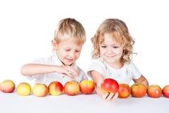 Två syskon som tycker om äpplen Arkivfoton