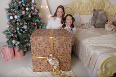 Två systerbrunettflickor med en enorm gåva arkivfoton