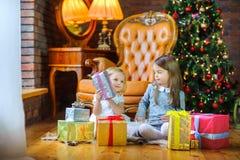 Två systrar öppnar gåvor royaltyfria bilder