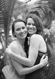 Två systrar eller vänner som kramar och ler Royaltyfria Foton