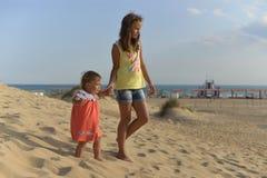 Två systrar går på en sandig strand som rymmer händer arkivfoto