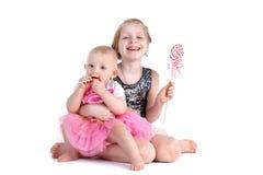 Två systrar 8 gamla år och 11 månad med godisen Arkivbilder