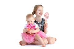 Två systrar 8 gamla år och 11 månad med godisen Royaltyfri Fotografi