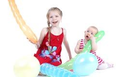 Två systrar 8 gamla år och 11 månad med luftballon Royaltyfri Foto