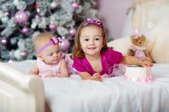 Två systrar hemma med julgranen Stående av lyckliga barnflickagarneringar Arkivfoto