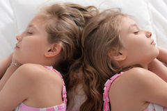 Två systrar kopplar samman att sova Fotografering för Bildbyråer