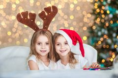 Två systrar kopplar samman i dräkter Santa Claus och hjorthorn i den dekorerade inre mot bakgrunden av ljus för ` s för det nya å Arkivfoton