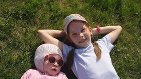 Två systrar ligger på det gröna gräset på en solig dag En i en baseballmössa, andra i en stucken hatt och rött stock video