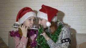 Två systrar, lite flicka och en tonåring i jultomten hattar att sjunga och dansa att sitta på soffan med glitter på deras arkivfilmer