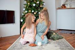 Två systrar med blont hår sitter på bakgrunden av julgranen som förbereder fester för jultomten nytt år royaltyfria bilder