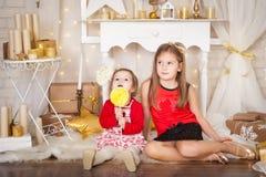 Två systrar med en stor lollypop Arkivbilder