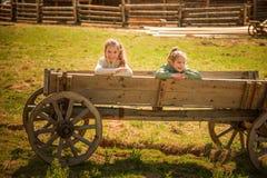 Två systrar på den gamla trävagnen Arkivbild