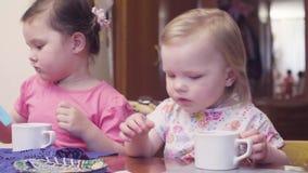 Två systrar på en tabell, väntande på frukost arkivfilmer