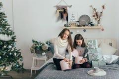 Två systrar ser julklappar, medan sitta på sängen Arkivbild