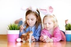 Två systrar som bär kaninöron på påsk Arkivfoto