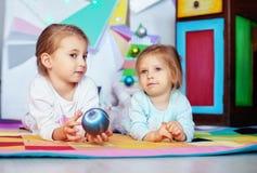 Två systrar som framlänges ligger Julfilial och klockor Royaltyfri Foto