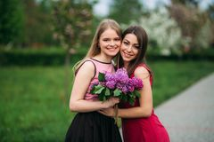 Två systrar som går utanför i vår, parkerar De rymmer en bouqet av lilan och leendet royaltyfri bild