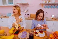 Två systrar som har argument om sunt, bantar och skada av socker arkivfoton