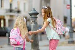 Två systrar som har gyckel med dricksvattenspringbrunnen på varm och solig sommardag royaltyfri fotografi