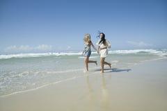 Två systrar som kör på strandholdinghänder Royaltyfri Foto