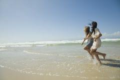 Två systrar som kör på strandholdinghänder Arkivfoto