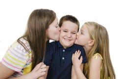 Två systrar som kysser den förvånade brodern Två unga flickor som kysser den förvånade pysen Arkivfoton