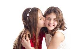 Två systrar som kysser och kramar Arkivfoto