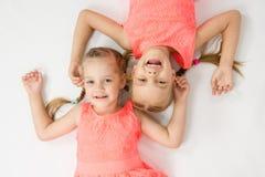 Två systrar som ligger på den tillbaka stålar Royaltyfria Bilder