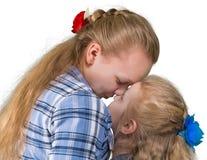 Två systrar som omfamnar och kysser Royaltyfri Bild
