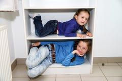 Två systrar som passar i lagringskugge Arkivbilder
