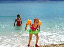 Två systrar som spelar lekar och simmar i havet Arkivfoto