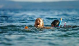 Två systrar som spelar lekar och simmar i havet Arkivbilder