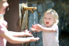 Två systrar som spelar med dricksvattenspringbrunnen Royaltyfri Foto