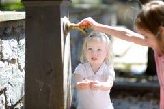 Två systrar som spelar med dricksvattenspringbrunnen Royaltyfria Bilder